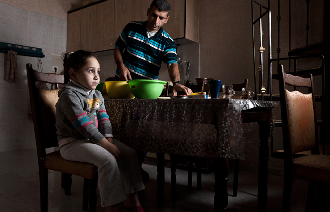 Hamed proudly showed me that he shares equally with his wife in household tasks. After they prepared maqluba together, he is clearing the table and preparing to wash the dishes. Meanwhile, one of their daughters patiently waits for a taste. (Aida camp - Bethlehem - West Bank - Palestine - 2013)