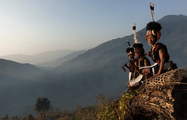 Khiamniungan Naga warriors seated in the front of misty mountains.