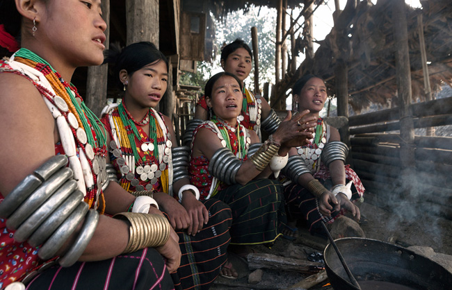 Early on the morning, Pangmi Naga women from Hachi, weighed down by their heavy armbands, warm them up around the woodfire. Round their necks the Hachi women have necklace chain of old coins and tubular shells.