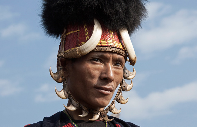 Khiamniungan Naga warrior with traditional hat orned by 2 wild pig's teeth and a set of tiger's teeth.