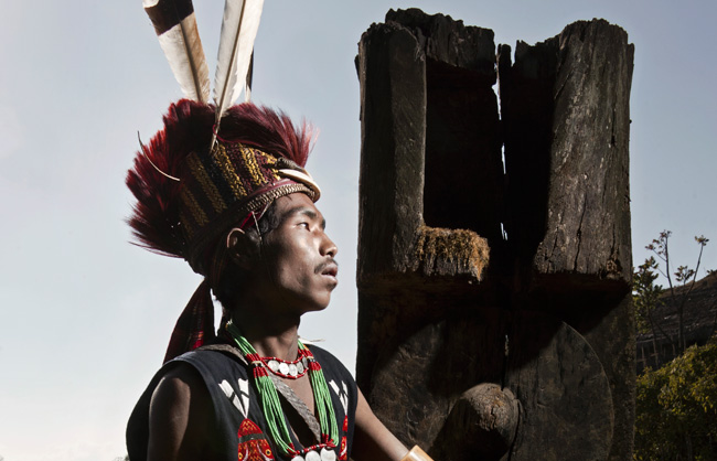 Pangmi Naga warrior in front of a pole with carved gong, symbol of wealth.