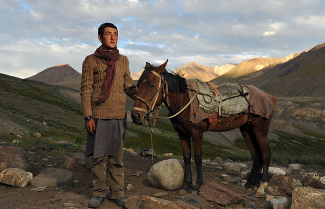 WWakhi man with his horse on the way to reach the camp, bringing food to his family and the community. Little Pamir - Afghanistan - 2016